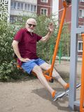 Senior man trains on sporting equipment on open air Stock Photography