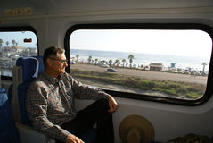 Senior Man Traveling on Train. An older or senior man traveling on a train and the train is passing by the california coast highway 101 with the ocean in the Stock Photo