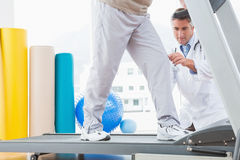 Senior man on treadmill with therapist crouching Stock Image