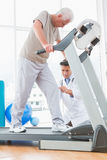 Senior man on treadmill with therapist crouching Royalty Free Stock Photography