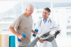 Senior man on treadmill with therapist Stock Photo