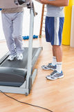 Senior man on treadmill with trainer Stock Images