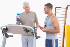 Senior man on treadmill with trainer. Senior men on treadmill with trainer in fitness studio Royalty Free Stock Images
