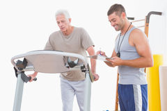 Senior man on treadmill with trainer Royalty Free Stock Photo