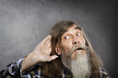 Senior man tries to listen sound, elder hearing loss deafness Stock Image