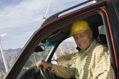 Senior Man In Truck At Wind Farm. Portrait of happy senior male worker sitting in pickup truck at windfarm Royalty Free Stock Photo