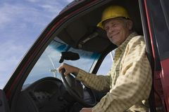 Senior Man In Truck At Wind Farm. Portrait of happy senior male worker sitting in pickup truck at windfarm Stock Images