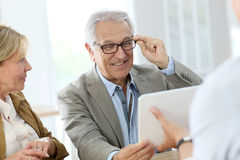 Senior man trying on eyeglasses in optical store Stock Images