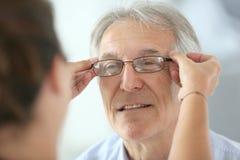 Senior man trying on new eyeglasses Stock Image