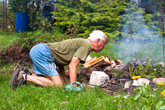 Senior man trying to make a bonfire Royalty Free Stock Photo