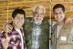 Senior man with two sons holding fishing rods Royalty Free Stock Photography