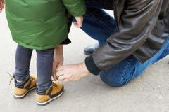 Senior man tying the laces on a child boots. Father or grandfather helps his little son or grandson. The both wearing casual. Outdoors, copy space stock photos