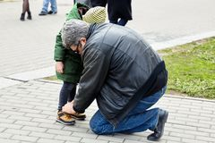 Senior man tying the laces on a child boots. Father or grandfather helps his little son or grandson. The both wearing casual. royalty free stock photos