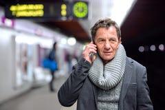 Senior man at the underground platform, talking on phone Royalty Free Stock Images