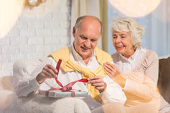 Senior man unwrapping christmas gift. Happy women and senior men unwrapping his  gift Stock Photo