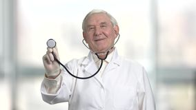 Senior man use stethoscope to check your health, front view. Black stethoscope pointed at the camera. Bright windows backround at the day stock footage