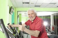 Senior man uses elliptical cross trainer Stock Images