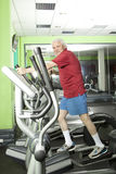 Senior man uses elliptical cross trainer Stock Photos