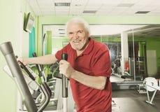 Senior man uses elliptical cross trainer Royalty Free Stock Photography