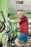Senior man uses elliptical cross trainer Stock Photography