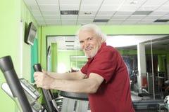 Senior man uses elliptical cross trainer Royalty Free Stock Image