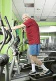 Senior man uses elliptical cross trainer Stock Image