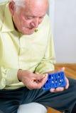 Senior man uses a pill organizer Royalty Free Stock Images