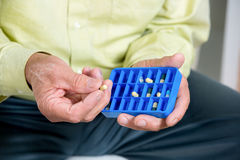 Senior man uses a pill organizer Stock Photos