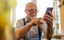 Free Senior Man Using A Mobile Phone At Home Royalty Free Stock Images - 217101419