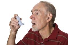 Senior man using asthma inhaler. Senior man spraying asthma medication into his mouth Stock Images