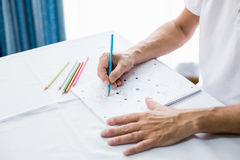 Senior man using a colouring book. In a retirement home Stock Photos