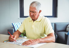 Senior man using a colouring book. In a retirement home Stock Photo