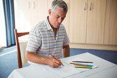 Senior man using a colouring book. In a retirement home Stock Image