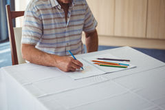 Senior man using a colouring book. In a retirement home Royalty Free Stock Image
