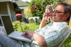 Senior man using computer outdoor Stock Photos