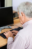 Senior Man Using Desktop PC In Class Royalty Free Stock Image