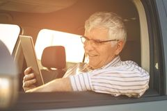 Senior man using digital tablet in a car. stock images