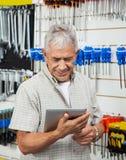 Senior Man Using Digital Tablet In Hardware Shop Stock Image