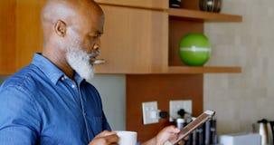 Senior man using digital tablet while having black coffee in kitchen 4k. Senior man using digital tablet while having black coffee in kitchen at home 4k