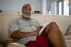 Senior man using digital tablet in the living room at home Stock Photos