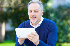 Senior man using a digital tablet outdoor Royalty Free Stock Photo