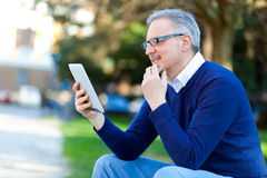 Senior man using a digital tablet outdoor Royalty Free Stock Photos
