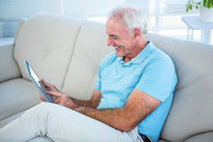 Senior man using digital tablet while sitting on sofa Stock Image
