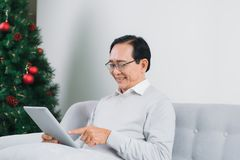 Senior man is using a digital tablet and smiling while resting o. N couch at home Royalty Free Stock Image