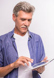 Senior man. Using digital tablet while standing on grey background royalty free stock photos