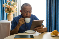 Senior man using digital tablet at table in nursing home Stock Photo