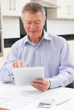 Senior Man Using Digital Tablet To Check Personal Finances Stock Images