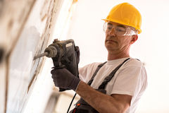 Senior man using drill in the reconstruction of the building. Senior man using drill at contruction site Royalty Free Stock Images