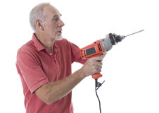 Senior man using an electric drill. To make a hole in the wall royalty free stock photo