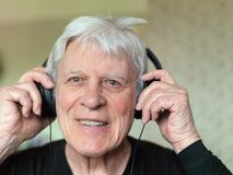 Senior man using headphones for listening music royalty free stock image